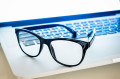 Pair of eyeglasses sitting on top of laptop