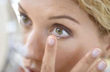 Woman applying contact lens to eye