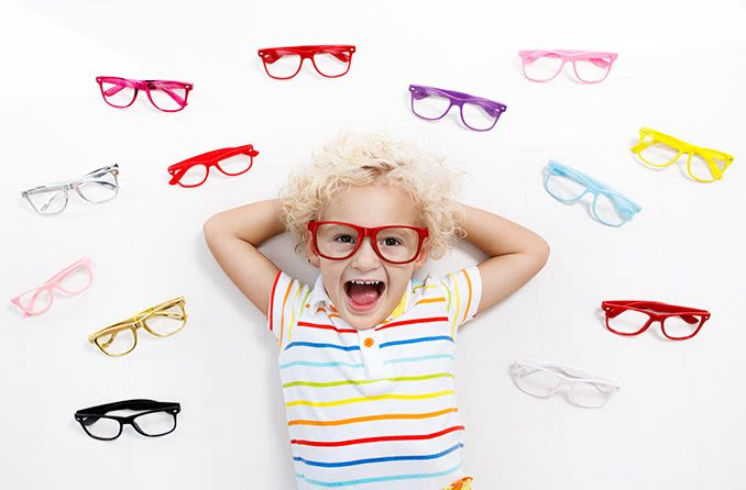 Smiling child surrounded by eyeglasses