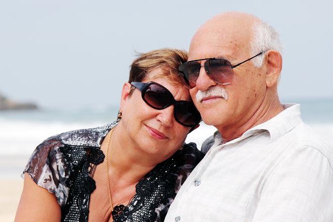 pareja de edad con gafas de sol en la playa