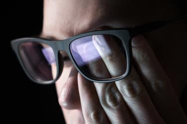 मनुष्य चश्मा पहने हुए कंप्यूटर को देखते हुए अपनी आंख को रगड़ता है।