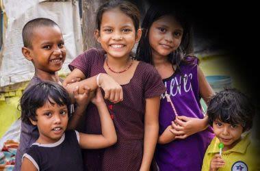 Foto de 5 crianças e ao canto superior direito uma mancha preta que representa a visão de quem possui descolamento da retina.