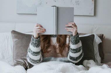 Uma mulher segurando um livro perto de ler.
