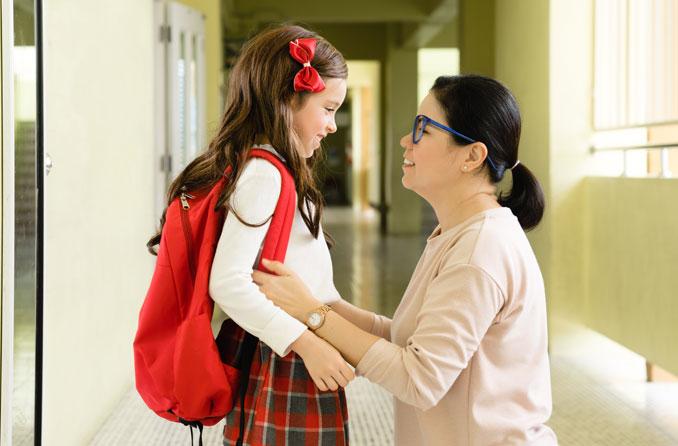 Woman and child inside a school hallway.