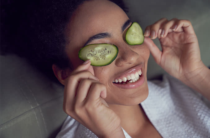 woman with droopy eyelids putting cucumber on her eyes as a home remedy