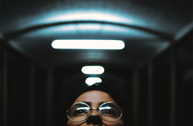woman wearing eyeglasses looking up at lights