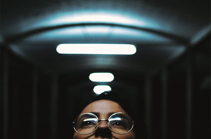 Frau mit Brille blickt auf Lichter