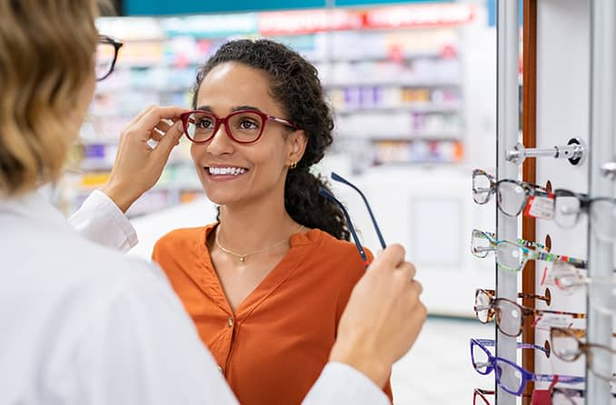 woman trying on eyeglasses to treat her astigmatism