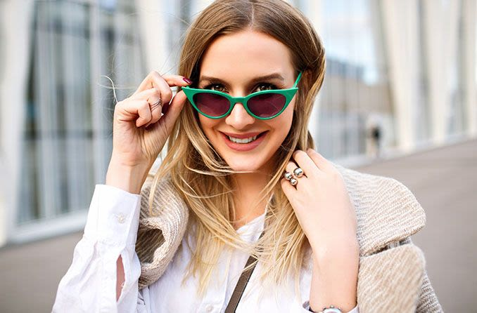 Woman peering over her green cat-eye sunglasses