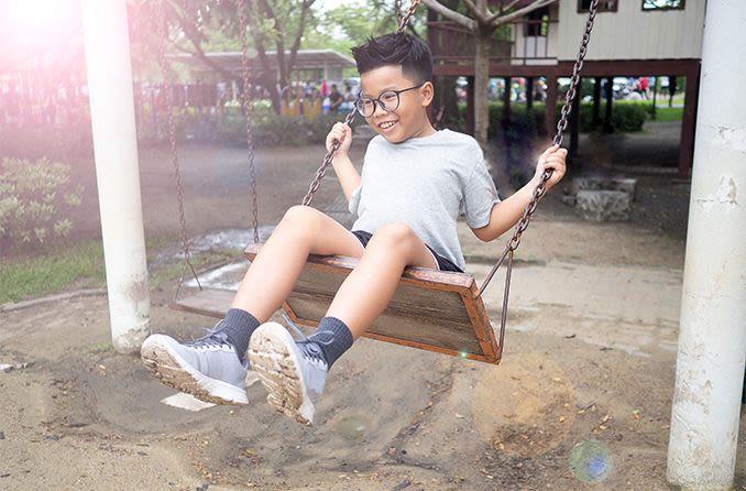 child playing outdoors wearing eyeglasses