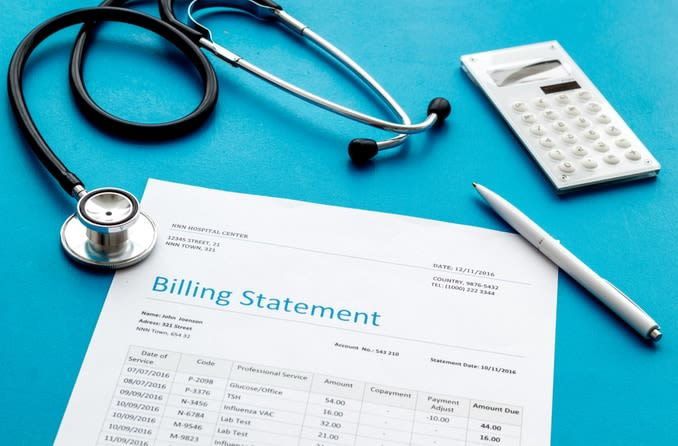 medical bill next to a calculator and stethoscope