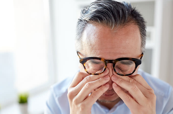 homme se frottant les yeux de la douleur oculaire