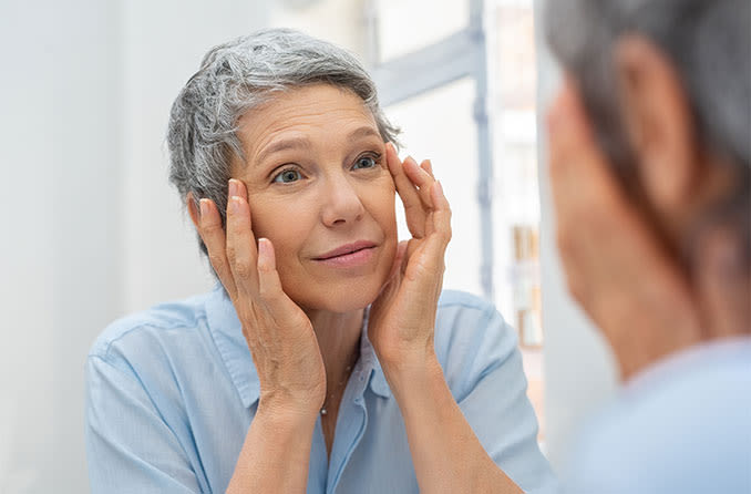 woman looking in the mirror wondering what caused her drooping eyelids (ptosis)