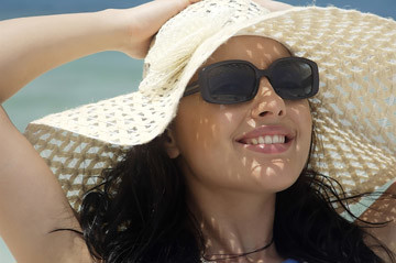 A woman wearing sunglasses to protect herself from the sun's harmful ultraviolet rays.