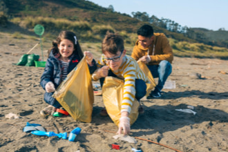 A girl and two boys volunteer to pick up trash on the beach