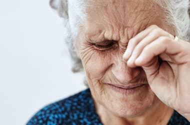 امرأة تعاني من اضطراب في العين تغطي وجهها بيديها