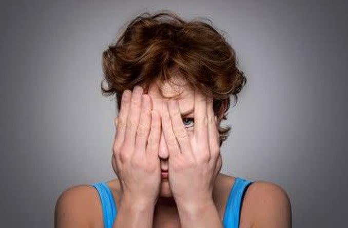 женщина с заболеванием глаз закрыла лицо руками