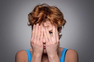 Frau mit einer Augenerkrankung, die ihr Gesicht mit den Händen bedeckt
