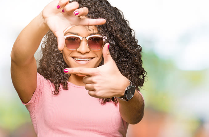 Woman with sunglasses holding up her fingers to frame her face shape