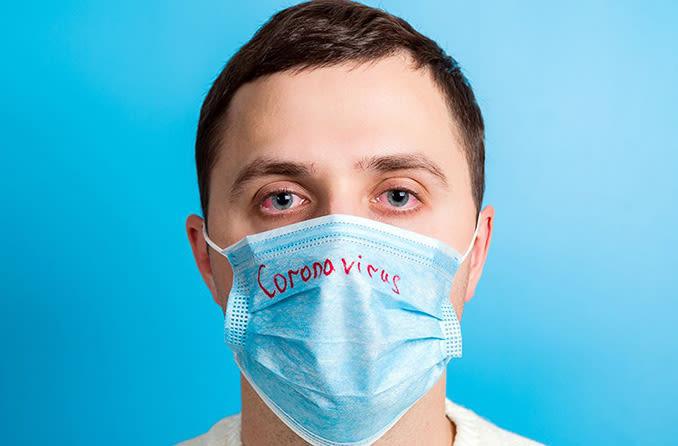 Hombre con mascarilla que tiene coronavirus y conjuntivitis