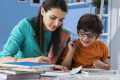 A young boy wearing glasses gets help with his homework.