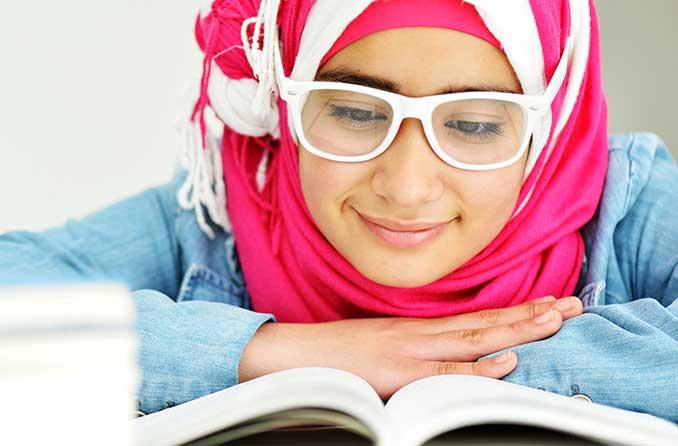 فتاة صغيرة ترتدي نظارة تقرأ كتابًا