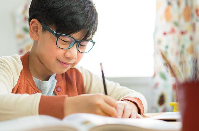 一个戴着眼镜的小男孩在他的作业中获得帮助