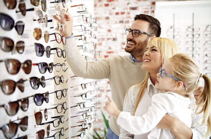 Happy family looking at eyeglass frames in an optical store - FSA