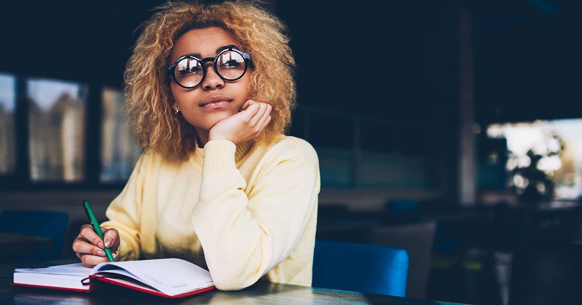 Frau mit Brille macht sich Notizen in einem Buch