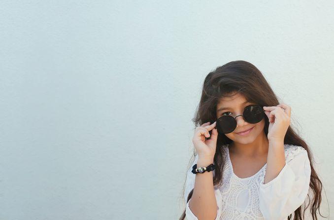 bir çocuk güneş gözlüğü takıyor