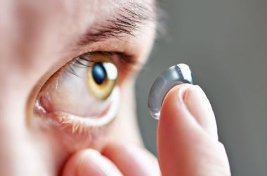 Man applying contact lens to eye