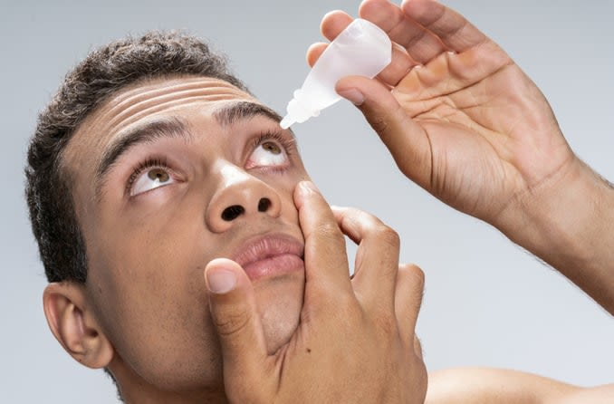 Man tilting head back to apply eye drops