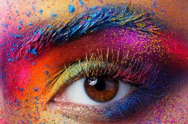 Closeup of an eye with colorful paint or makeup surrounding it