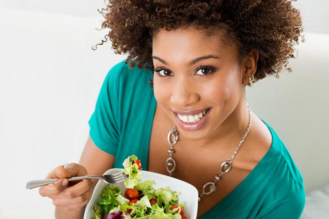 Woman in teal shirt eating a salad