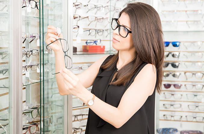 woman in optical store looking at price tag of pair of eyeglasses