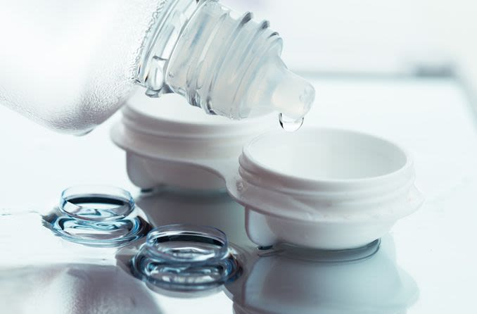 Contact lens solution being poured into a contact lens case with a pair of contacts in the foreground.