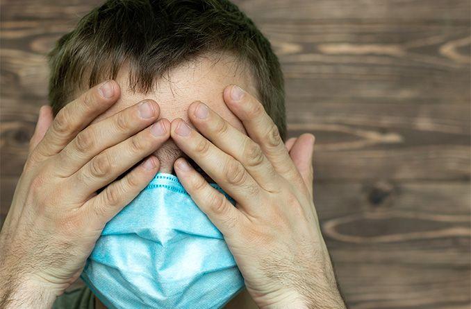 Hombre portando un cubrebocas sufriendo del contagio del virus en los ojos