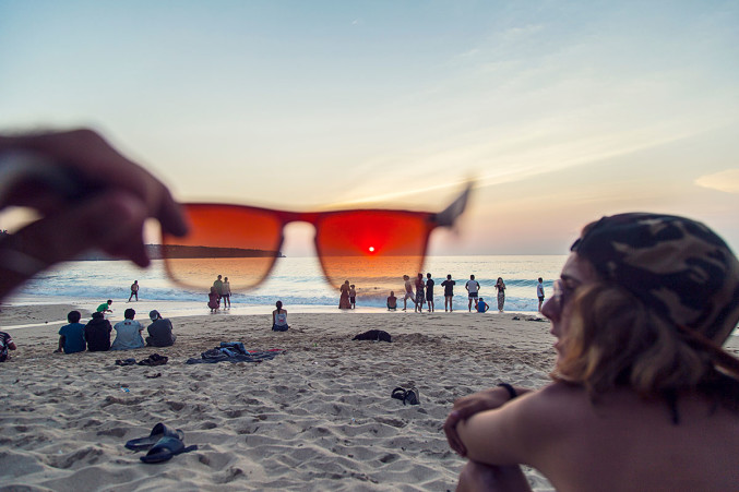 Looking through a pair of sunglasses at the beach