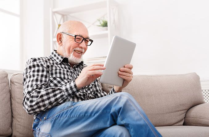 Older man smiling looking at a tablet