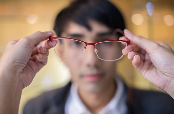 putting eyeglasses on a man with astigmatism