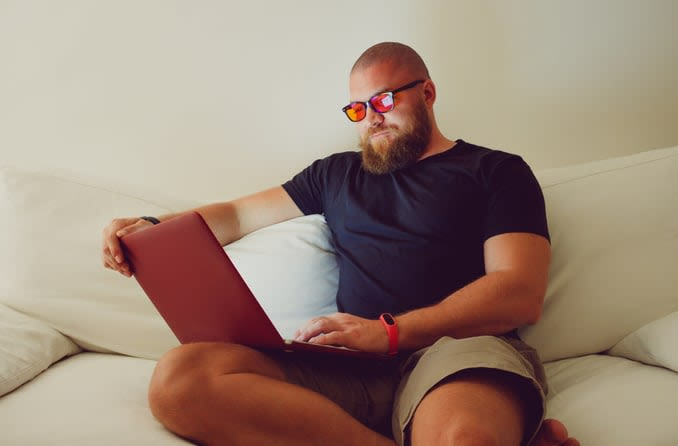Bearded man wearing amber-tinted blue light blocking glasses while using a laptop