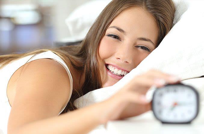 niña feliz durmiendo con reloj despertador