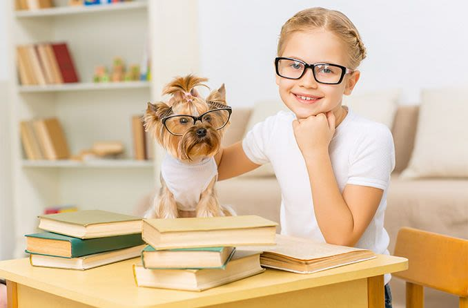 young girl wearing eyeglasses with her dog also wearing eyeglasses
