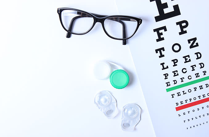 Contacts and eyeglasses on an eye chart