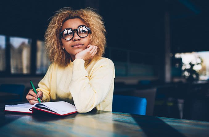Young woman wearing glasses thinking and writing in a notebook