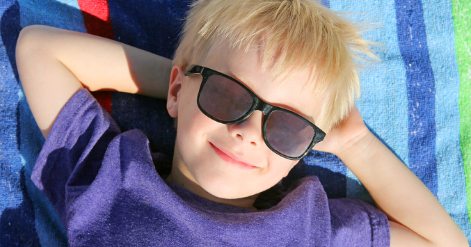 77f420b2e3a boy laying on beach towel wearing sunglasses. Advertisement. Do children  really need ...