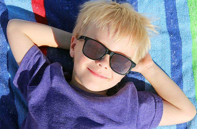 menino deitado na toalha de praia, usando óculos escuros