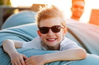Smiling boy wearing sunglasses.