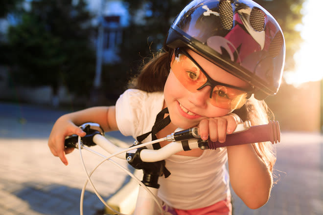 Little girl wearing trivex eyeglass lenses while riding a bike