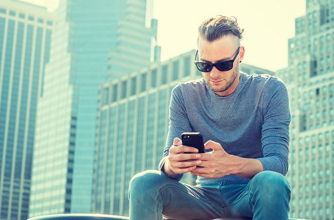 Man wearing progressive sunglasses outdoors looking at mobile phone